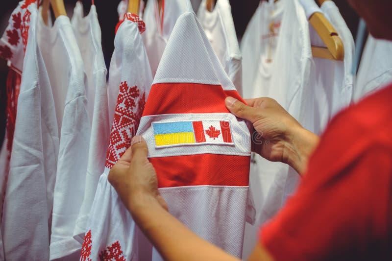 Mężczyzna ogląda koszulkę z Kanadyjską flaga i Ukraińską flaga zdjęcia stock