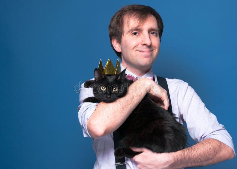 mężczyzna ono uśmiecha się w różowej koszula i suspenders, trzyma czarnego kota w złotej domowej roboty koronie fotografia stock