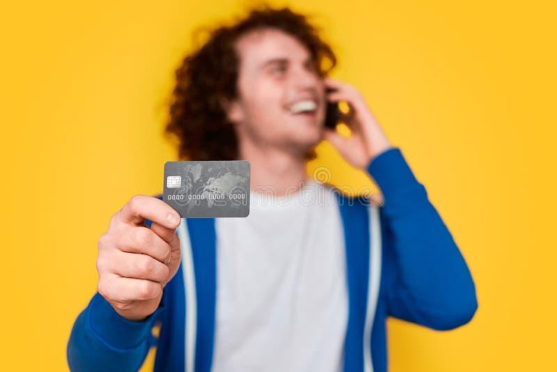 Mężczyzna opowiada na telefonie i pokazuje kartę kredytową obraz royalty free