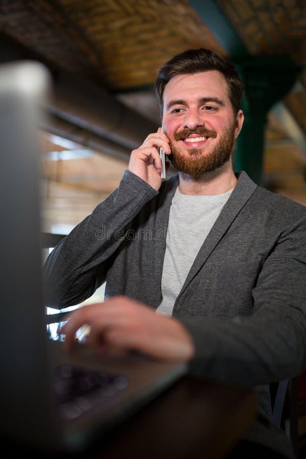 Mężczyzna opowiada na telefonie komórkowym i używa laptop fotografia stock