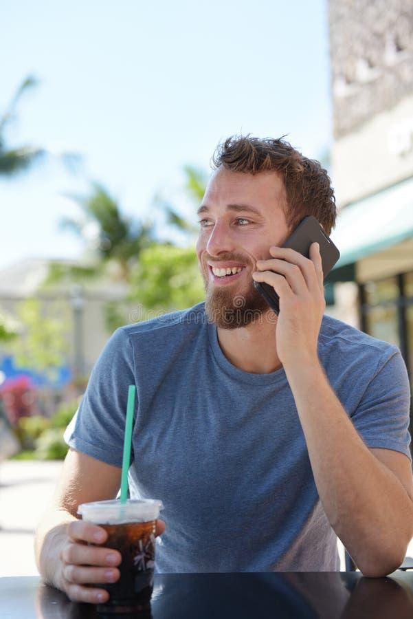 Mężczyzna opowiada na telefonie komórkowym na cukiernianym używa smartphone obraz royalty free
