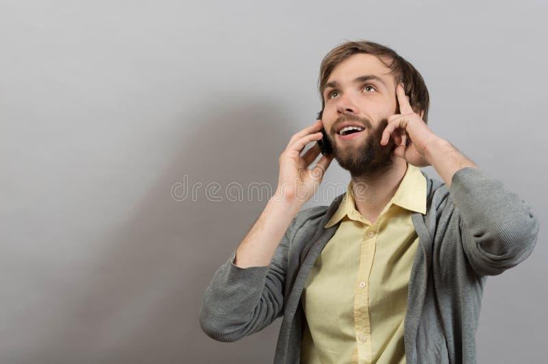 Mężczyzna opowiada na telefonie Na szarości obrazy stock
