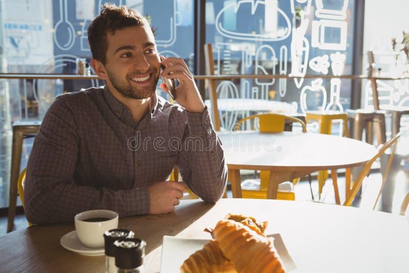 Mężczyzna opowiada na telefonie w kawiarni z śniadaniem zdjęcie stock