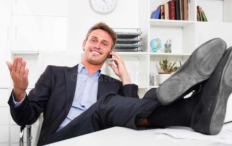 Mężczyzna opowiada na wiszącej ozdobie z ciekami up na biurku obraz royalty free