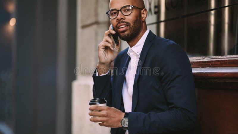 Mężczyzna opowiada nad telefonem komórkowym outdoors w garniturze zdjęcie royalty free