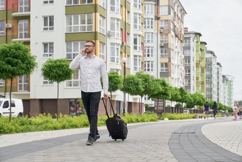 Mężczyzna opowiada telefonem z walizki odprowadzenia puszka ulicą zdjęcie royalty free