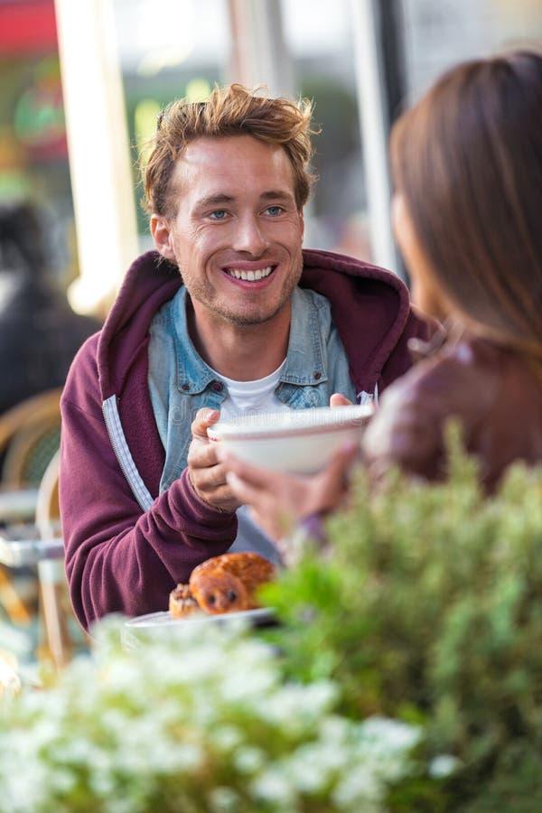 Mężczyzna opowiada z dziewczyną przy kawiarnia stołem Przyjaciele spotyka w mieście ma zabawę pije kawę Para na dacie, młodzi lud zdjęcia royalty free