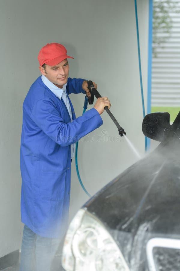 Mężczyzna opryskiwania naciska płuczka dla samochodowego obmycia fotografia stock