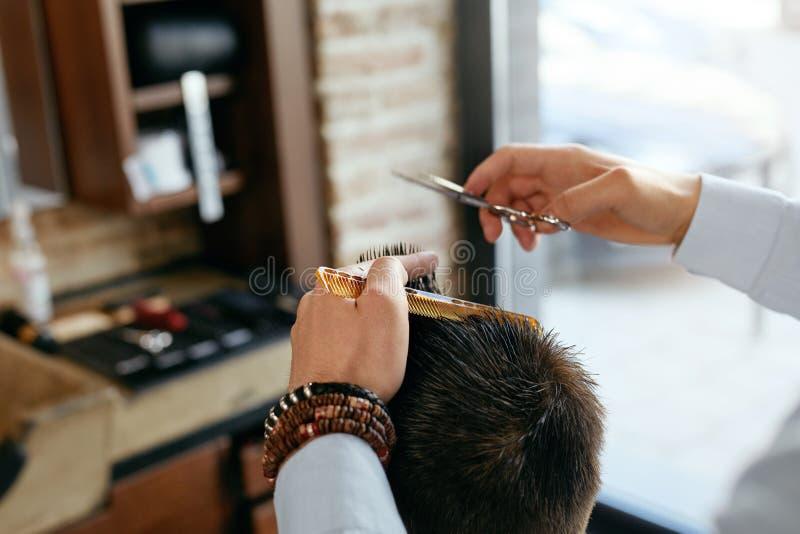 Mężczyzna ostrzyżenie Fryzjera męskiego rozcięcia mężczyzna ` s włosy W fryzjera męskiego sklepie obraz royalty free