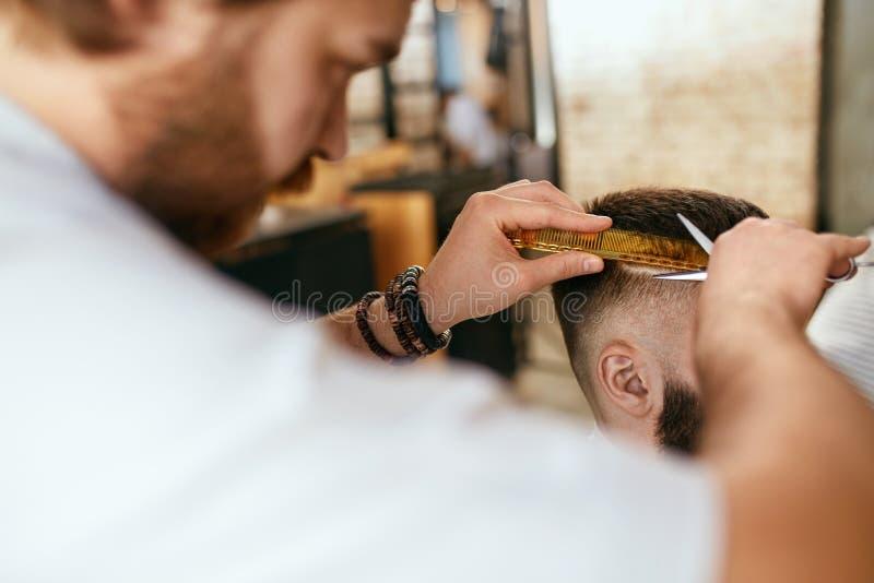 Mężczyzna ostrzyżenie Fryzjera męskiego rozcięcia mężczyzna ` s włosy W fryzjera męskiego sklepie zdjęcie stock