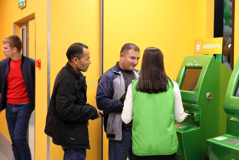 Mężczyzna otrzymywają poradę eksperta na bankowość usługa blisko ATM Sb zdjęcie royalty free