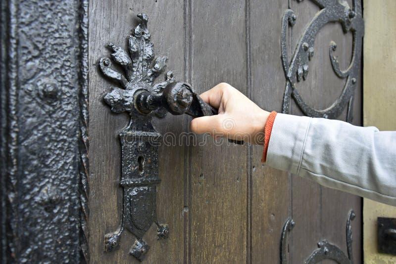 Mężczyzna otwiera antycznego drewnianego drzwi dekorującego z dokonanego żelaza elementami obraz royalty free