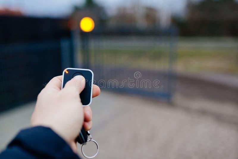 Mężczyzna otwiera automatyczną majątkową bramę zdjęcie royalty free
