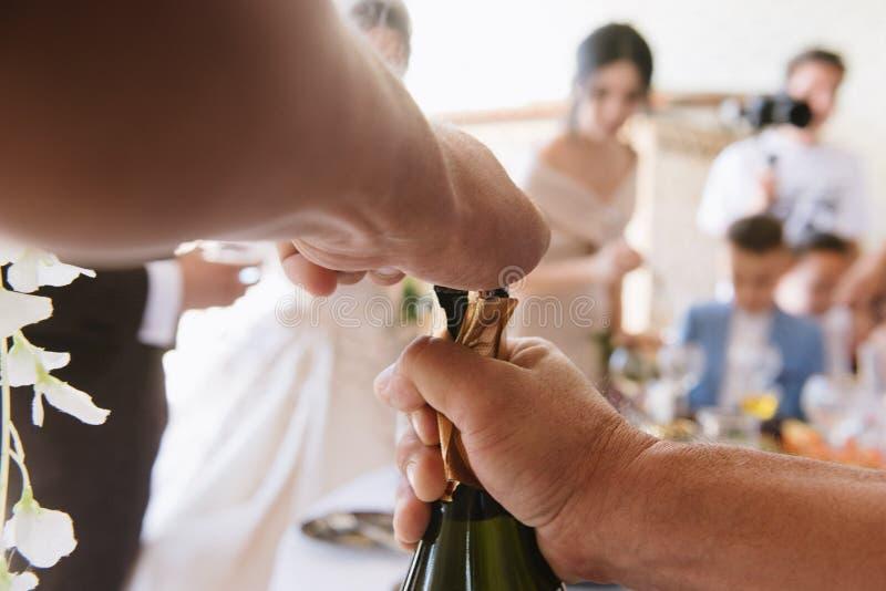 Mężczyzna otwiera butelkę szampana zakończenia uo zdjęcie royalty free