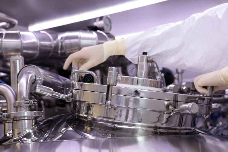 Mężczyzna otwiera chemicznego reaktor Rektor przemysł farmaceutyczny Mężczyzna zamyka reaktor Produkcja granuluje, suspen, obrazy royalty free