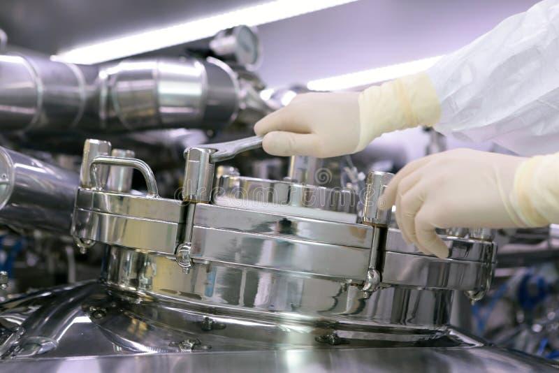 Mężczyzna otwiera chemicznego reaktor Rektor przemysł farmaceutyczny Mężczyzna zamyka reaktor Produkcja granuluje, suspen, fotografia royalty free
