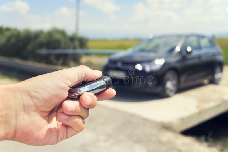Mężczyzna otwiera jego samochód z kontrolnym pilota kluczem, outdoors, filte zdjęcie stock