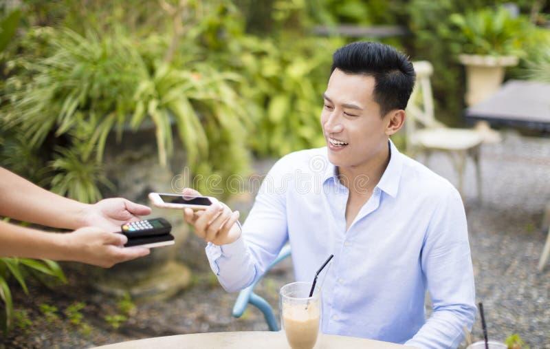 Mężczyzna płaci rachunek przez smartphone fotografia stock