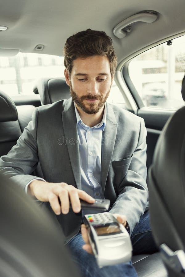 Mężczyzna płaci taxi z telefonem komórkowym Nfc technologia obrazy royalty free