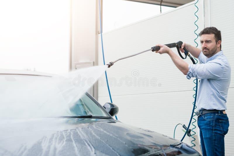 Mężczyzna płuczkowy samochód w samochodowego obmycia staci zdjęcia stock