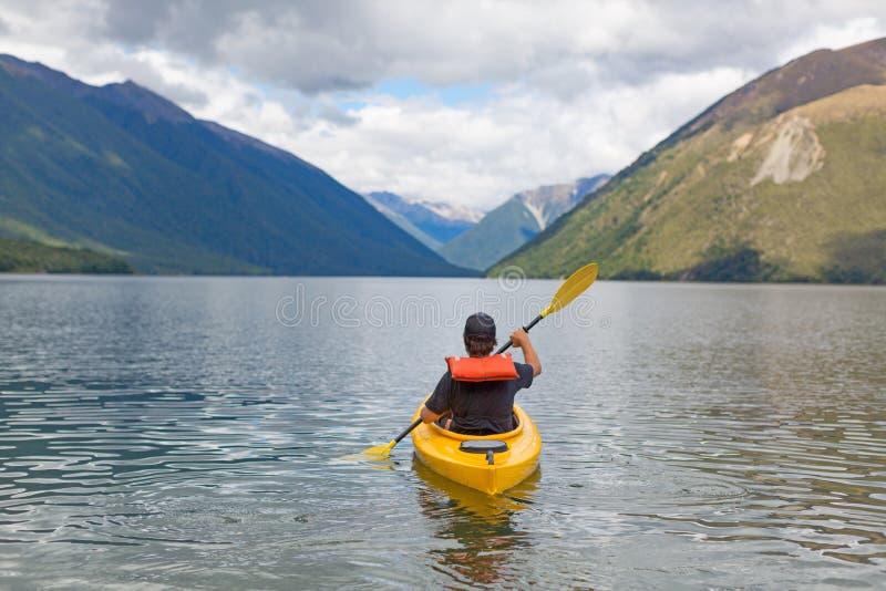 Mężczyzna paddling kajaka w halnym jeziorze fotografia royalty free