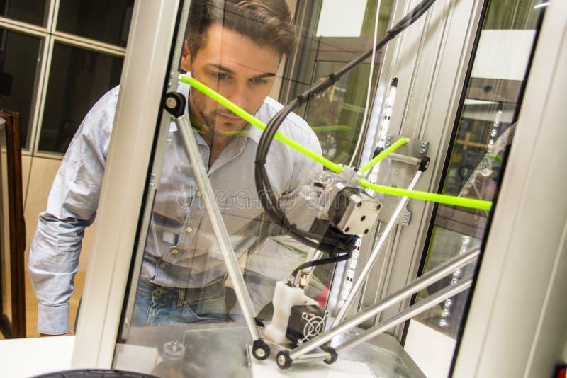 Mężczyzna patrzeje 3d drukarki maszynę zdjęcia royalty free