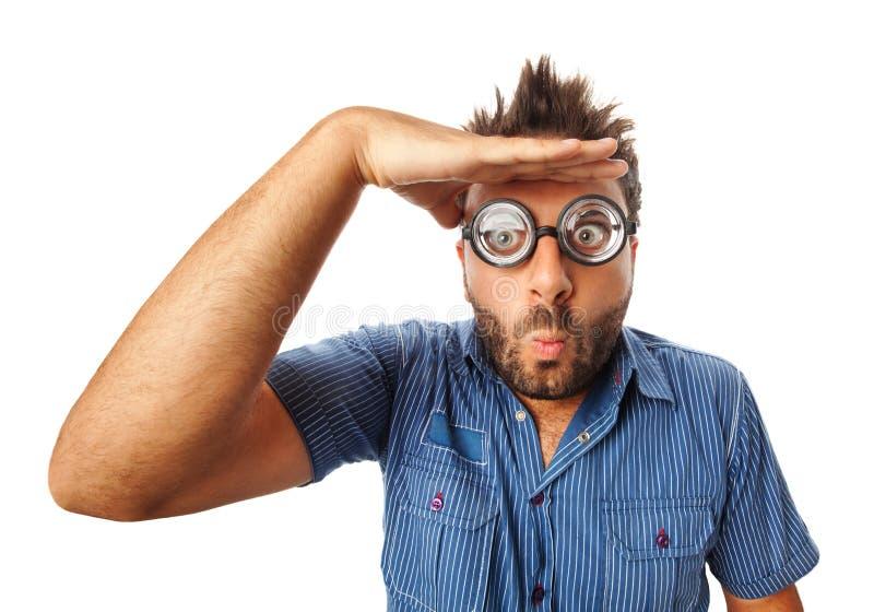 Mężczyzna patrzeje daleki z śmiesznym wyrażeniem i gęstymi szkłami zdjęcie stock