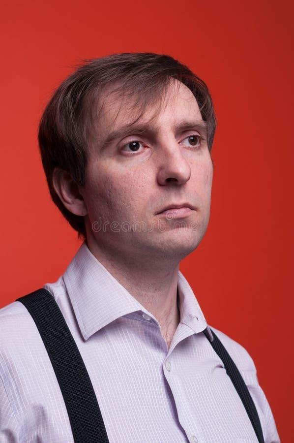 Mężczyzna patrzeje daleko od na koralowym tle z ciemnym włosy w różowej koszula i czarnym suspender zdjęcia stock