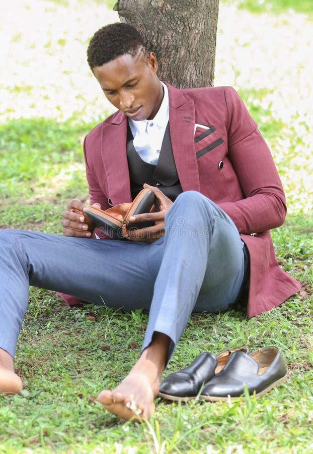 Mężczyzna patrzeje jego portfel podczas przerwa na lunch w kostiumu zdjęcie stock