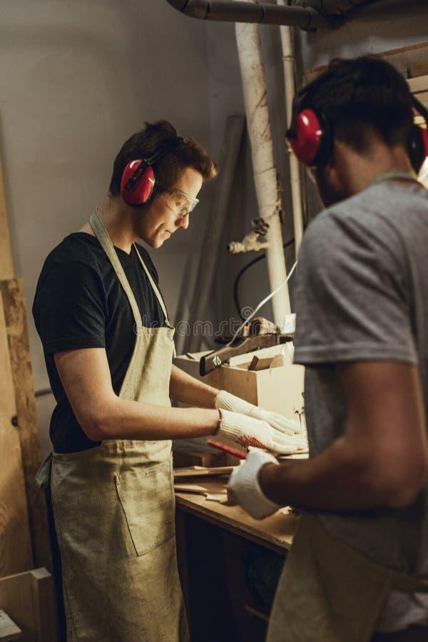Mężczyzna patrzeje kolegi używa joinery wyposażenie fotografia royalty free