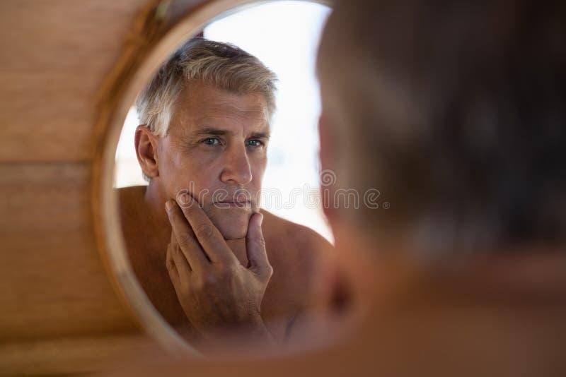 Mężczyzna patrzeje lustro w chałupie zdjęcia stock