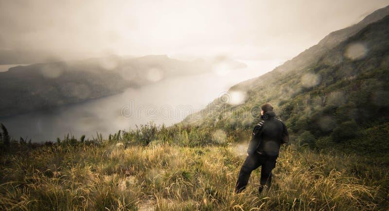 Mężczyzna patrzeje nad rzeką na wzgórzu obraz stock