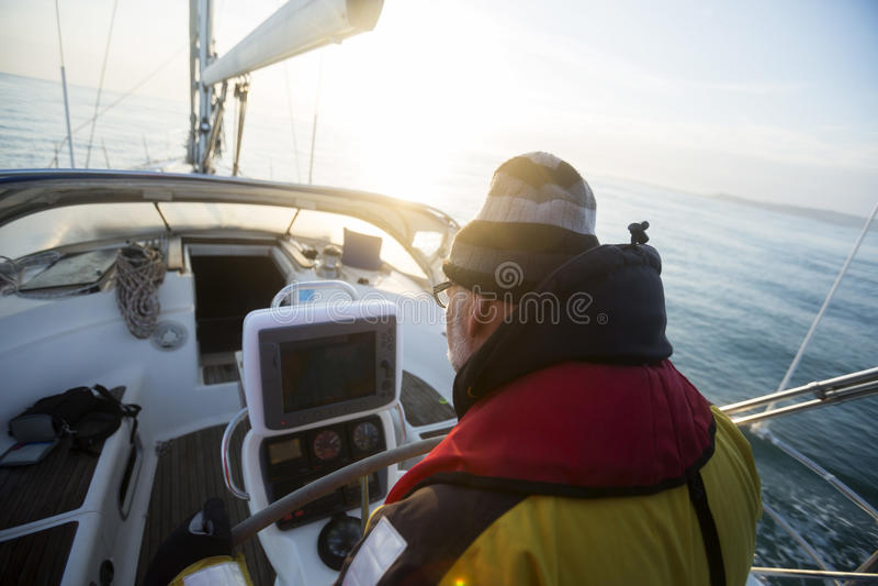 Mężczyzna Patrzeje Nawigacyjnego ekran Na żagiel łodzi fotografia stock