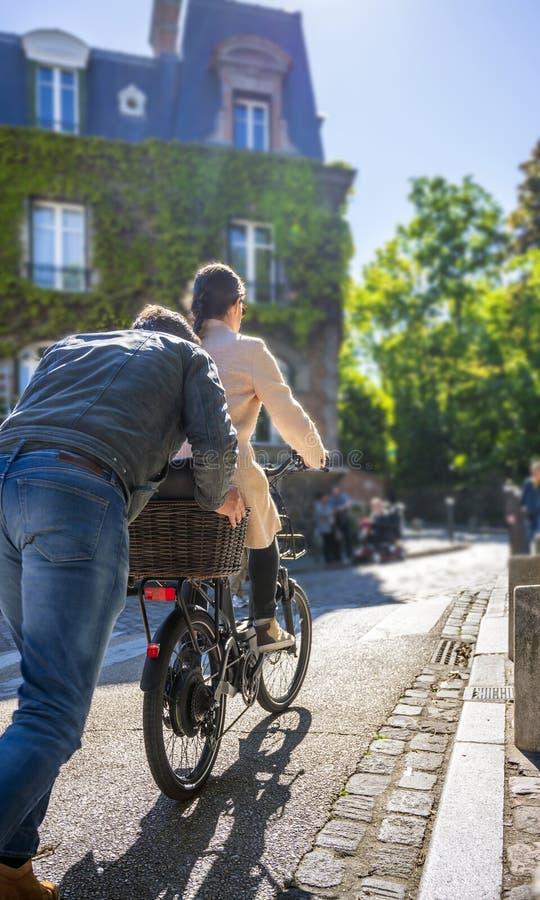 Mężczyzna pcha bicykl z dziewczyną wzgórze pomaga jej przejażdżce w górę ulicy w Montmartre obrazy royalty free