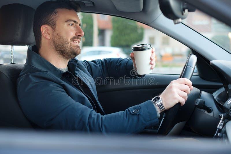 Mężczyzna pije kawę podczas gdy jadący samochód fotografia royalty free