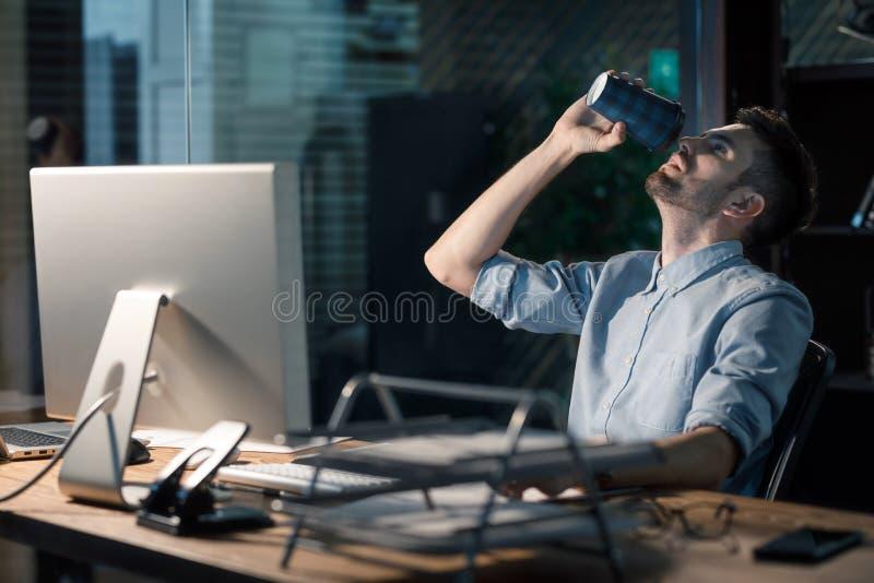 Mężczyzna pije kawowych pracujących overhours fotografia royalty free