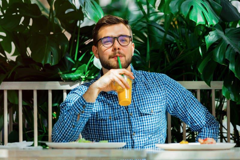 Mężczyzna pije sok w kawiarni zdjęcie royalty free