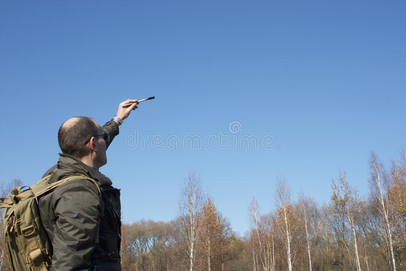 Mężczyzna pisze muśnięciu przeciw niebieskiemu niebu zdjęcie royalty free