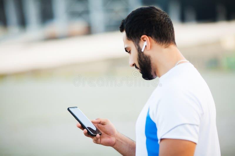 Mężczyzna po opracowywać w miasto parku i używać jego telefon komórkowego zdjęcia stock