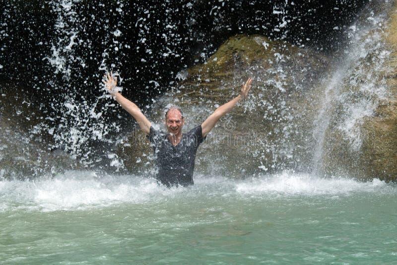 Mężczyzna pod siklawa przepływem zdjęcia stock