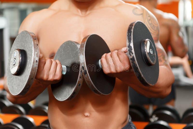 Mężczyzna podnosi dwa dumbbells w gym zdjęcie stock