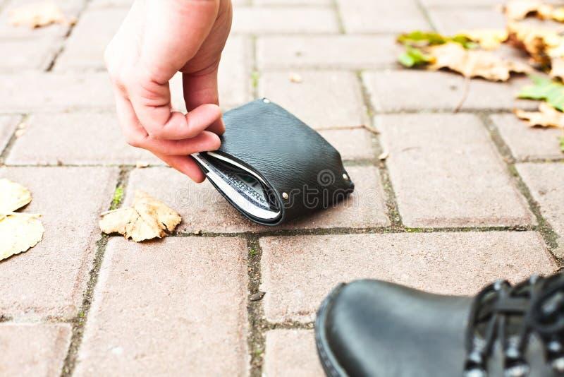 Mężczyzna podnosi jego czarnego portfel z pieniądze na ulicie zdjęcie stock