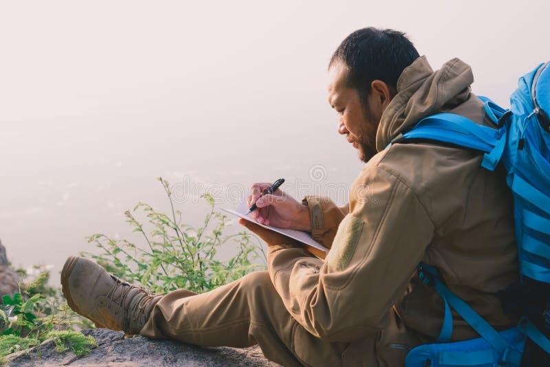 Mężczyzna podróżnik dokumentacyjny writing przy górami Brainstorming podróż obrazy stock