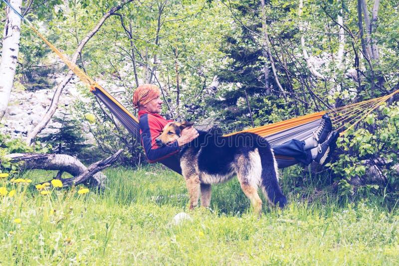 Mężczyzna podróżnik jest relaksujący w hamaku i bawić się z jego psem fotografia stock