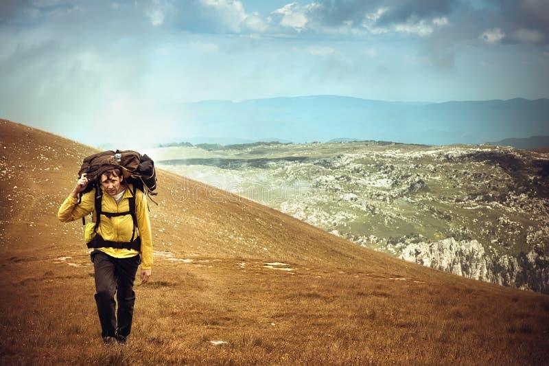 Mężczyzna podróżnik wycieczkuje w górach z plecakiem zdjęcie stock