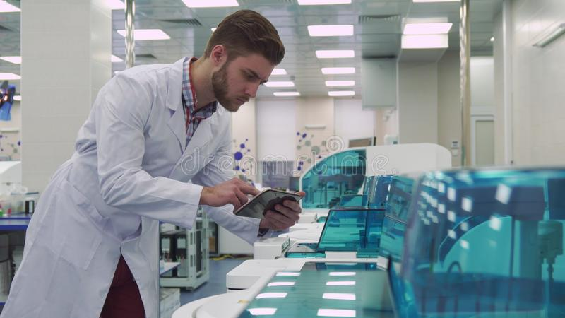 Mężczyzna podrzuca na pastylce blisko laboranckiej maszyny obraz stock