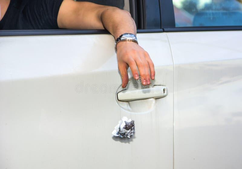 Mężczyzna podrzucania ściółka od Otwartego Samochodowego okno obrazy stock