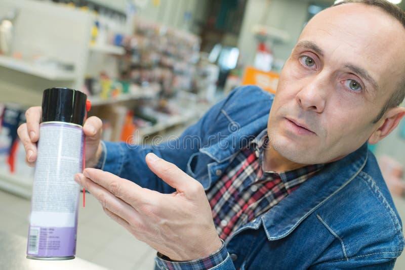 Mężczyzna pokazuje aerosol puszkę obraz stock