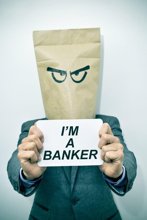 Mężczyzna pokazuje signboard z tekstem jestem bankowem fotografia stock