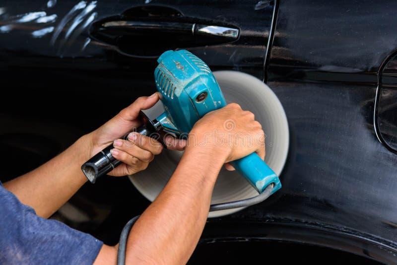 Mężczyzna polerowuje samochód maszyną do polerowania obrazy royalty free